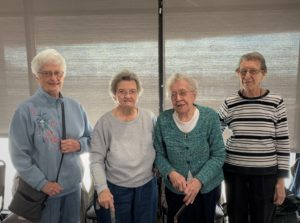 4 elderly adults standing next to eachother in front of a window