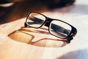 pair of eye glasses sitting on a wood desk